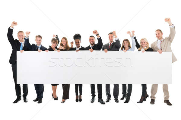 Happy Business Team With Arms Raised Holding Blank Billboard Stock photo © AndreyPopov