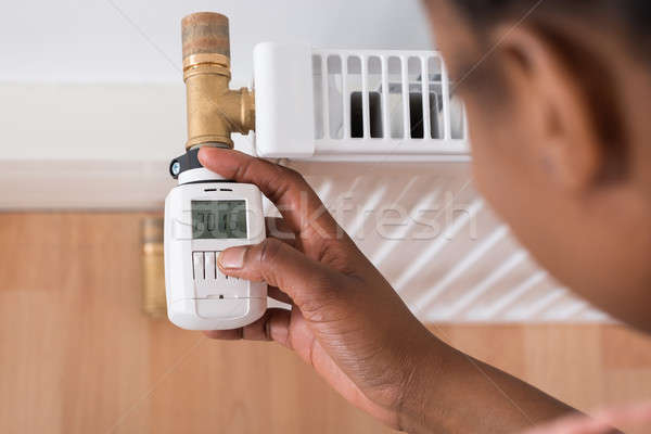 Woman Adjusting Temperature On Thermostat Stock photo © AndreyPopov