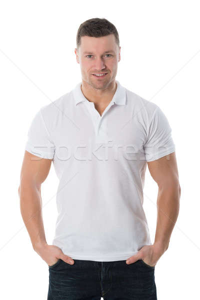 Smiling Man In Casuals Standing With Hands In Pockets Stock photo © AndreyPopov