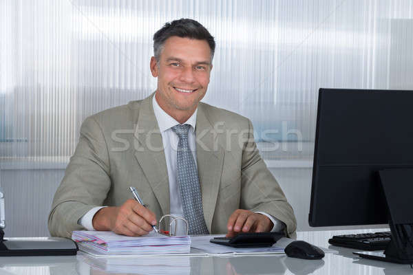 Confident Accountant Using Calculator While Writing On Documents Stock photo © AndreyPopov