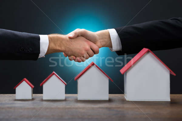 Businessmen Shaking Hands By Various Size Of House Models Stock photo © AndreyPopov