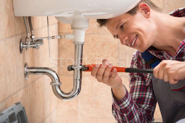 Vízvezetékszerelő megjavít mosdókagyló cső franciakulcs mosolyog Stock fotó © AndreyPopov