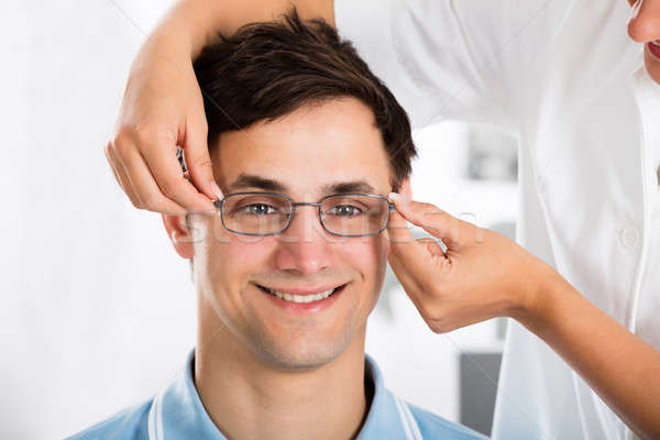 An Optician Helping Male Patient With New Eyeglasses Stock photo © AndreyPopov