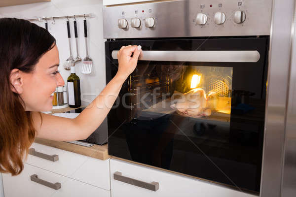 Woman Roasting Chicken Meat In Oven Stock photo © AndreyPopov