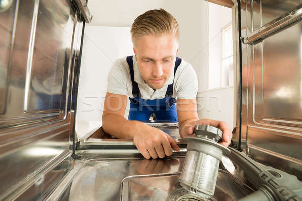 Man In Overall Repairing Dishwasher Stock photo © AndreyPopov