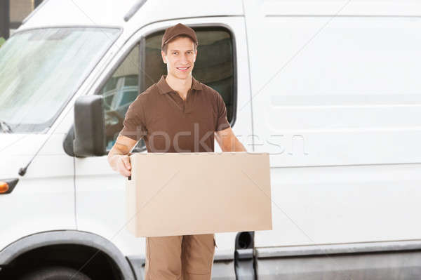 Portrait Of A Delivery Man Holding Box Stock photo © AndreyPopov