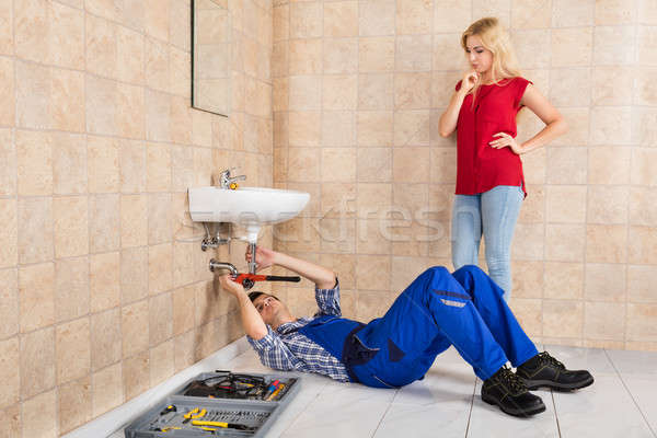 Young Male Plumber Repairing Sink In Bathroom Stock photo © AndreyPopov