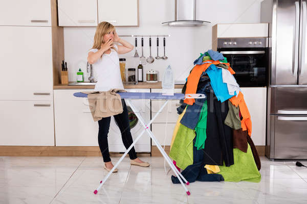 Frustrated Woman Looking At Pile Of Clothes For Ironing Stock photo © AndreyPopov