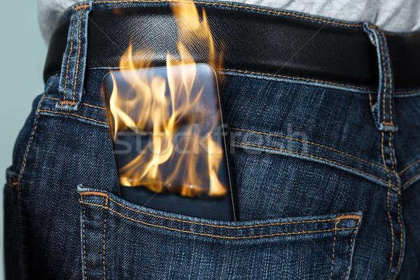 Burning Phone In Jeans Stock photo © AndreyPopov