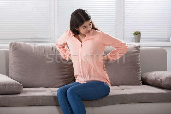 Zdjęcia stock: Młoda · kobieta · posiedzenia · kanapie · cierpienie · domu