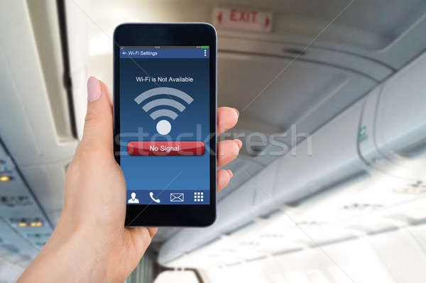Person's Hand Holding Mobile Phone Showing WiFi No Signal Sign Stock photo © AndreyPopov