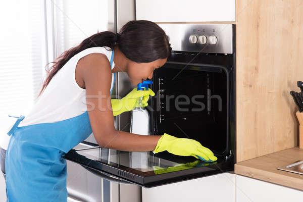 Donna pulizia forno spray bottiglia spugna Foto d'archivio © AndreyPopov