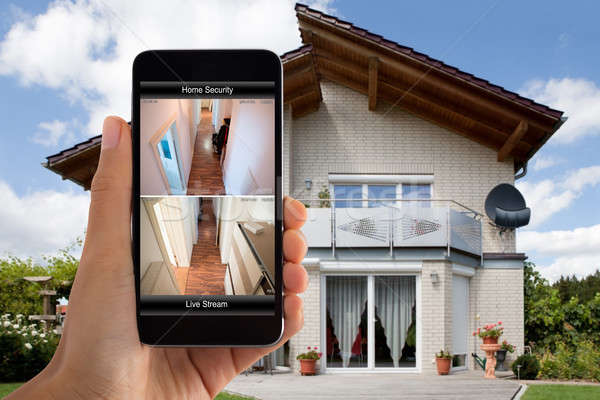 Person Hand Using Home Security System On Mobile Phone Stock photo © AndreyPopov