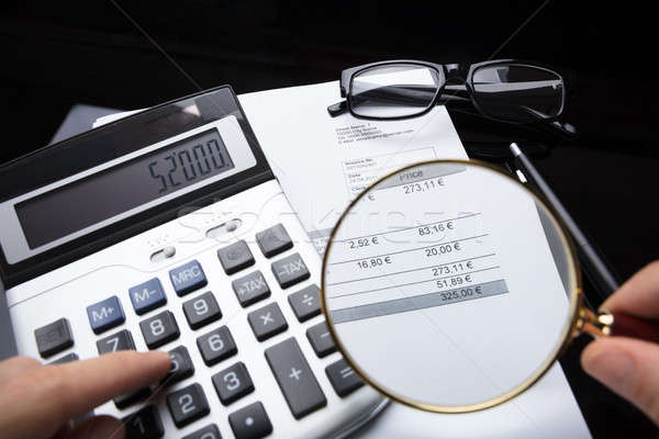 Businessperson Analyzing Bill With Magnifying Glass Stock photo © AndreyPopov