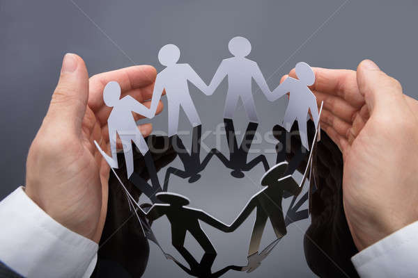 Businessperson's Hand Protecting Cut-out Figures Stock photo © AndreyPopov