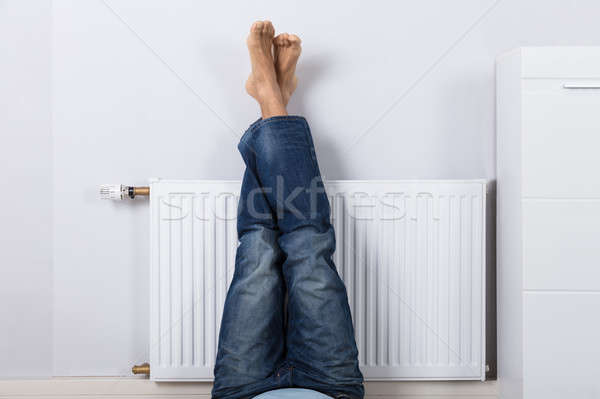 Man Warming Up His Feet On White Radiator Stock photo © AndreyPopov