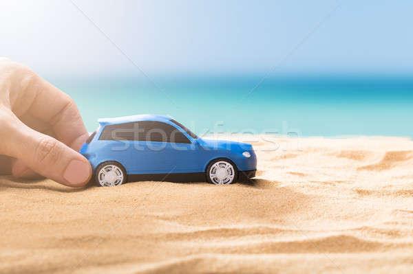 Mão humana pequeno azul carro praia Foto stock © AndreyPopov