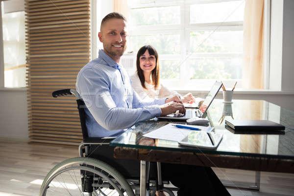 Uśmiechnięty niepełnosprawnych biznesmen pracy laptop portret Zdjęcia stock © AndreyPopov