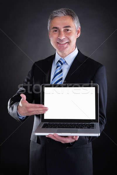 Happy Mature Businessman Showing Laptop Stock photo © AndreyPopov