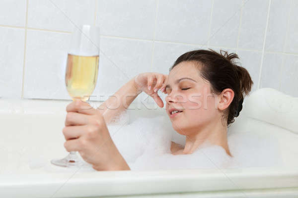 Woman in bathtub drinking champagne Stock photo © AndreyPopov
