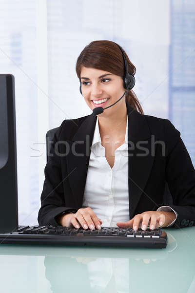 Businesswoman Wearing Headset At Computer Desk Stock photo © AndreyPopov