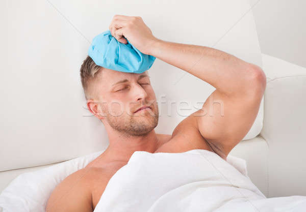 Man nursing a hangover holding an ice pack Stock photo © AndreyPopov