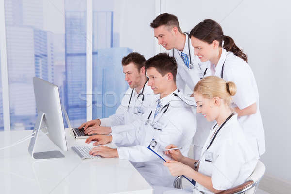 Doctors Working Together On Computer In Hospital Stock photo © AndreyPopov