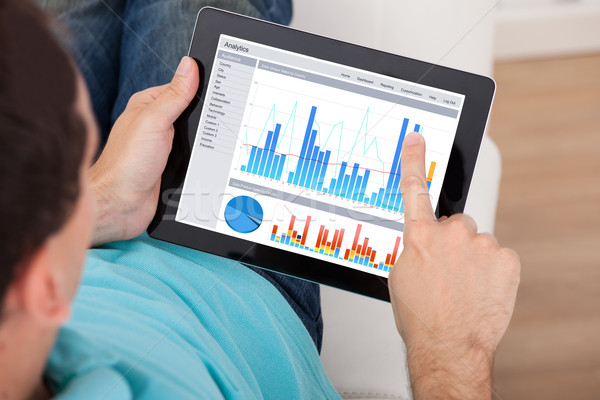 Man Analyzing Graphs On Digital Tablet Stock photo © AndreyPopov
