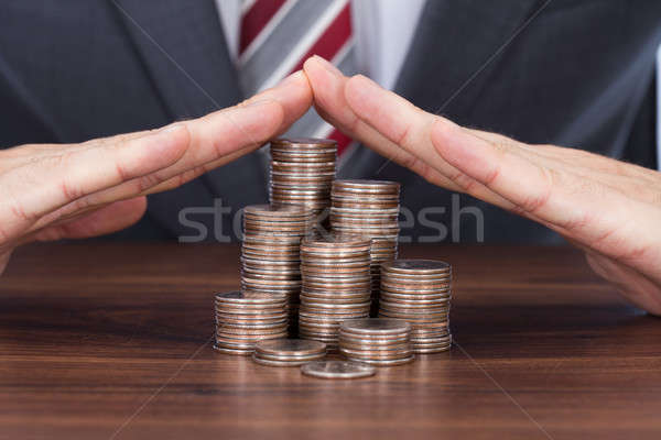 Businessman Sheltering Coin Stacks On Table Stock photo © AndreyPopov