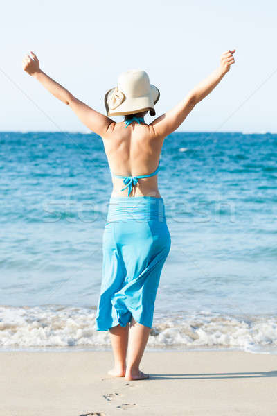 Woman Standing Arms Raised At Beach Stock photo © AndreyPopov