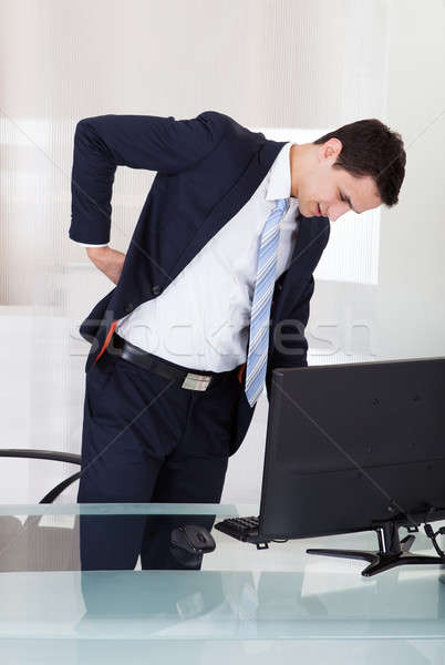 Businessman Suffering From Backache In Office Stock photo © AndreyPopov