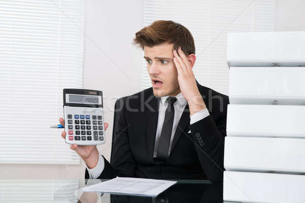 Shocked Businessman Looking At Calculator Stock photo © AndreyPopov