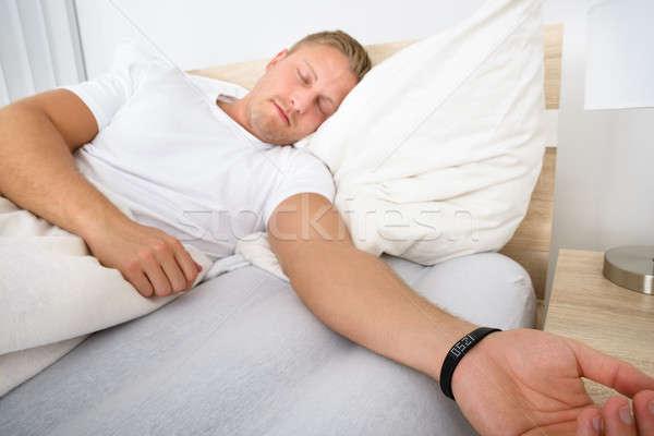 Férfi alszik visel okos karszalag fiatalember Stock fotó © AndreyPopov