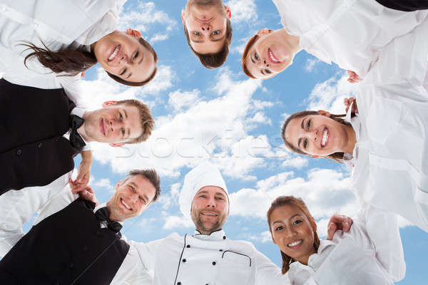 Happy Chef And Waiters Standing In Huddle Against Sky Stock photo © AndreyPopov