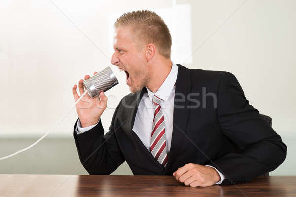 Businessman Screaming In Tin Cans Phone Stock photo © AndreyPopov