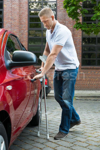 Disabled Man Holding Crutches Opening Door Of A Car Stock photo © AndreyPopov