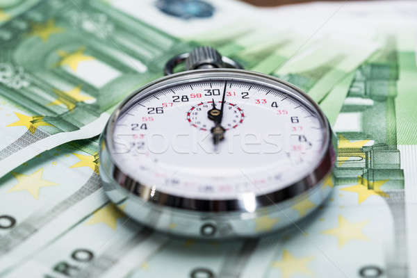 Stopwatch On Banknotes Stock photo © AndreyPopov