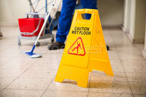 Worker Mopping Floor With Wet Floor Caution Sign Stock photo © AndreyPopov