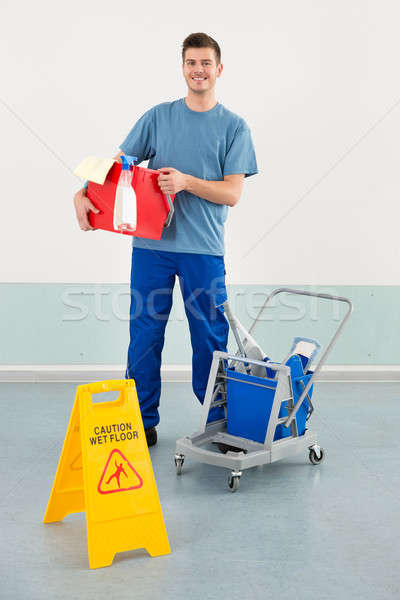 Worker With Cleaning Equipments And Wet Floor Caution Sign Stock photo © AndreyPopov