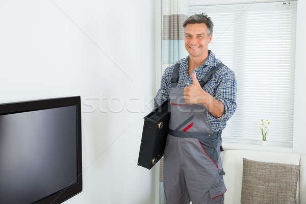Happy Technician With TV Set Top Box At Home Stock photo © AndreyPopov
