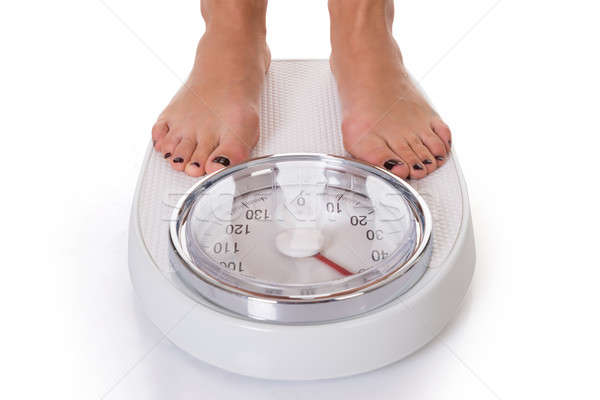 Low Section Of Woman Standing On Weighing Scale Stock photo © AndreyPopov