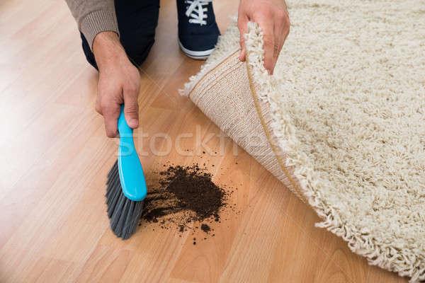 Man Using Brush To Sweep Mud On Hardwood Floor Stock photo © AndreyPopov