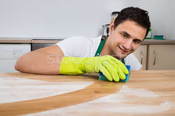 Man Cleaning Dust On Wooden Table With Sponge Stock photo © AndreyPopov