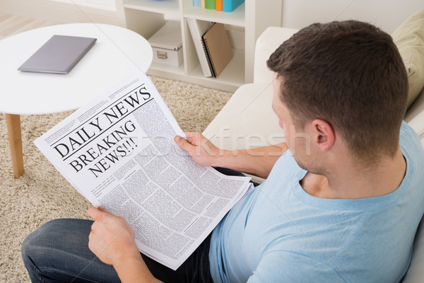 Man Reading Breaking News On Newspaper At Home Stock photo © AndreyPopov