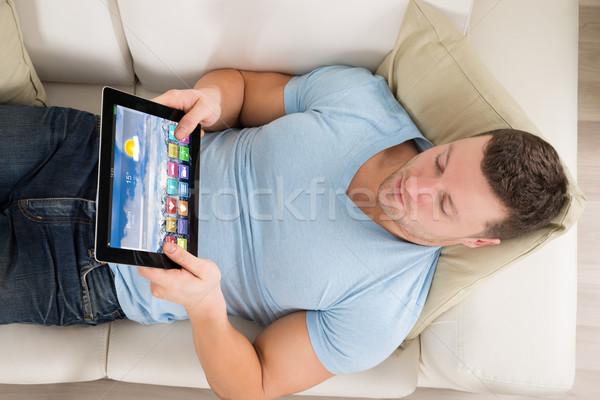 Férfi digitális tabletta kanapé közvetlenül fölött Stock fotó © AndreyPopov