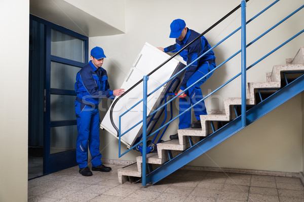 Movers Carrying Refrigerator While Climbing Steps Stock photo © AndreyPopov