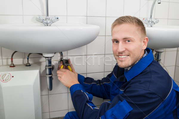 Plumber Fixing Sink In Bathroom Stock photo © AndreyPopov