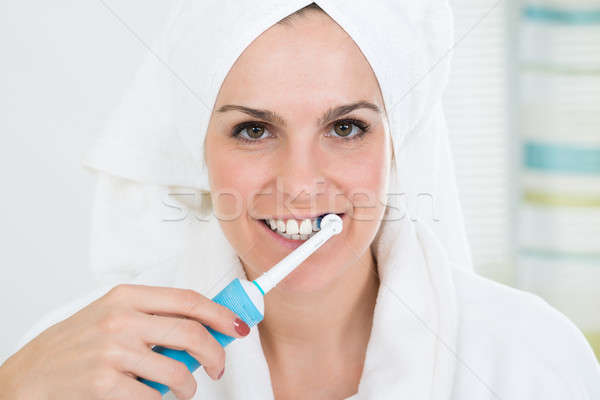 Nő fogmosás elektromos fogkefe közelkép fiatal nő Stock fotó © AndreyPopov