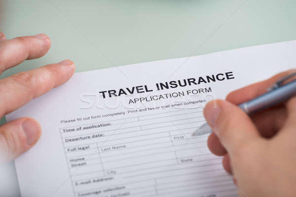 Person Hand Over Travel Insurance Application Form Stock photo © AndreyPopov