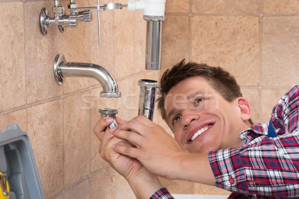 Plumber Fitting Sink Pipe In Bathroom Stock photo © AndreyPopov
